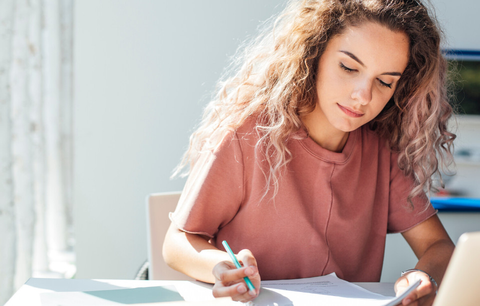 lease in writing image: woman writing a document with pen in hand