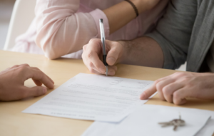 eviction notice image: picture of hands holding a pen signing a document