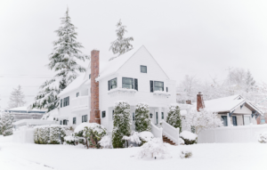 frozen pipes image: white house surrounded by pine trees covered in snow