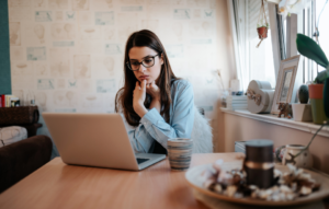 property listing scams image: woman with glasses looking stressed on laptop