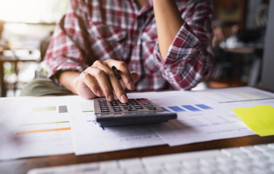 the cost of a bad tenant image: Picture of flannel-wearing woman's hands typing on calendar