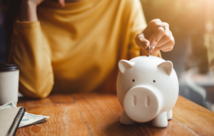 tenant prequalification image: woman wearing yellow shirt putting coin in white piggy bank