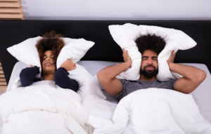 noise complaint image: woman and man laying in bed and covering ears with pillows