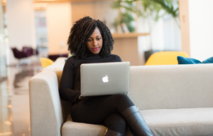 fill vacant units image: a woman dressed in all black sitting on a couch working on a macbook laptop