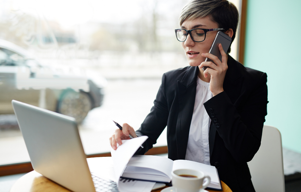 RentTech Image: business woman on phone in front of a laptop