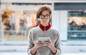 rentredi vs yardi blog header: woman with short brown hair and glasses holding and staring at an ipad