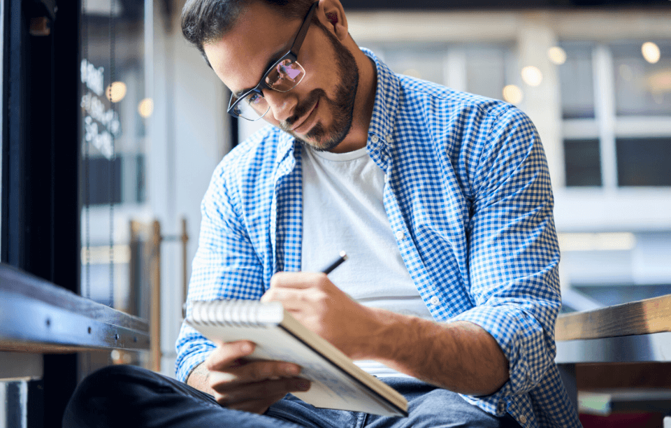 image: man with glasses writing on a notepad