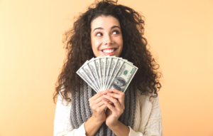 report rent payments blog post: woman smiling while holding fanned out dollar bills