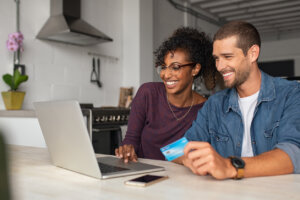 hero image for rentredi vs quickbooks payments: image of a young couple smiling happily at their laptop holding a credit card