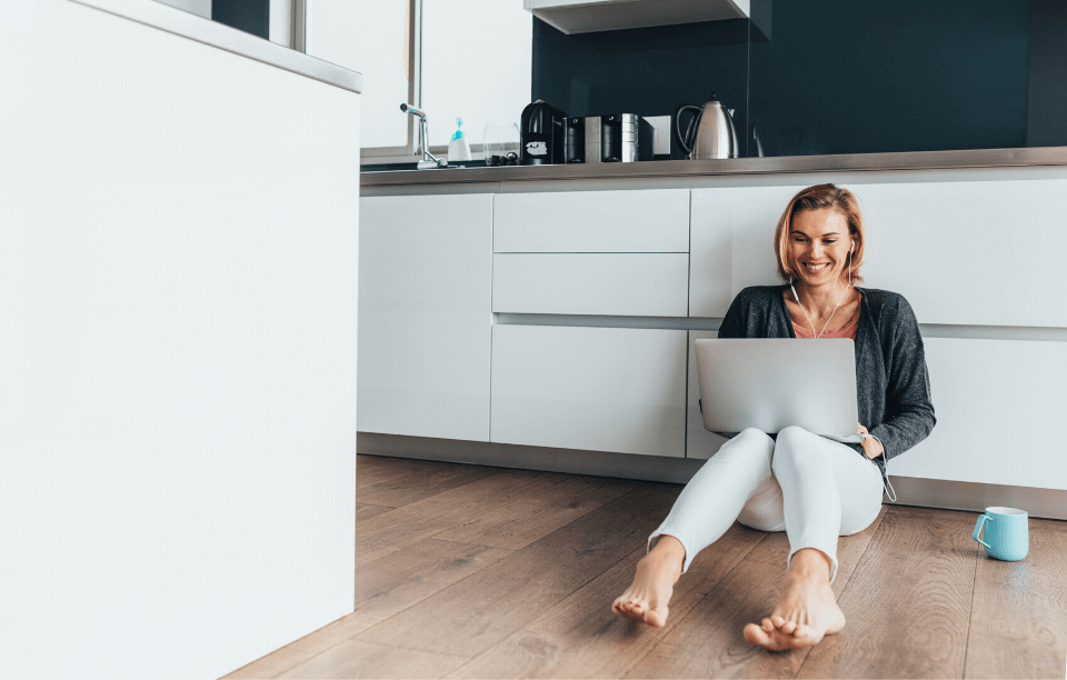 blond woman with headphones and laptop sitting on floor writing a landlord reference letter
