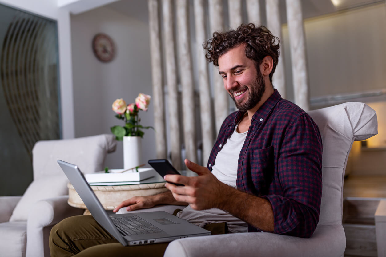 rentredi vs hemlane hero image: Young handsome man making video call with friends while sitting on sofa at his modern home.Concept of happy business people. Business man at home checking statistics on mobile phone and laptop