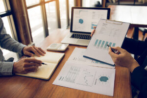 rental property accounting software hero image: Two business partnership coworkers analysis strategy with discussing a financial planning graph and company budget during a budget meeting in office room.