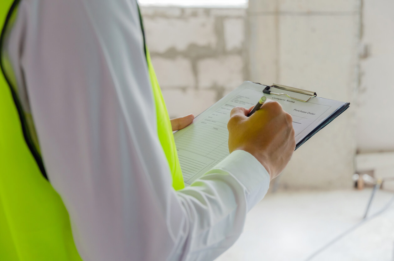 hvac maintenance hero image: foreman builder, engineer or inspector in green safety vest reflective checking and inspecting with clipboard at construction site building interior, inspection, contractor and engineering concept