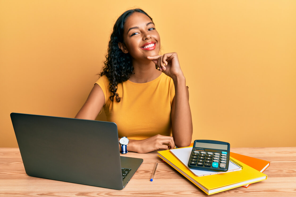 prorated rent blog hero image: young woman working at the office with laptop and calculator looking confident at the camera smiling with hand placed on chin