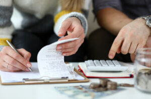 rent increase letter hero image: Month revenue of young couple calculating finances and expenses