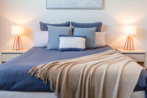 Staging Homes vs Staging Apartments hero image: Beautiful arrangement of pillows on bed in a bedroom with bedside lamps and copy space